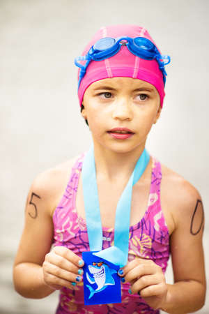 Vertical portrait of small tired 9 years old girl swimmer after finish on open water competition for children with medal. Sport and activity for kids. Swimming. Healthy lifestyle from childhood.
