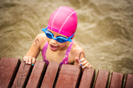 Young small 9 years old girl swimmer on finish line after open water competition for children. Sport and activity for kids. Swimming competition. Healthy lifestyle from childhood. Stok Fotoğraf