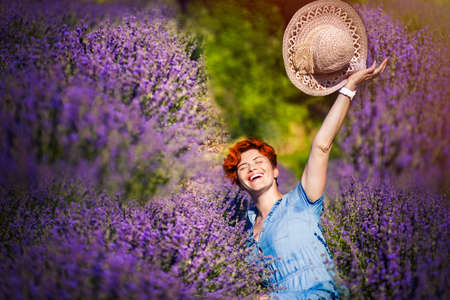 Happy red haired woman with short haircut in blue dress playing with her straw hat and laughing in hot summer day in lavender field. Rural summer in Provence. Travel. Foto de archivo
