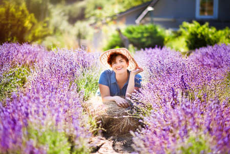 Happy red haired woman with short haircut in blue dress and straw hat laying in hot summer day in lavender field. Rural summer in Provence. Travel. Foto de archivo