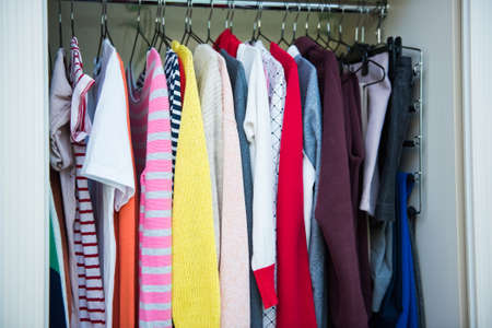 Colorful clothes on hangers in well organized wardrobe at home. Choice of cotton clothes of different colors on hangers. Organizational space - management of environment
