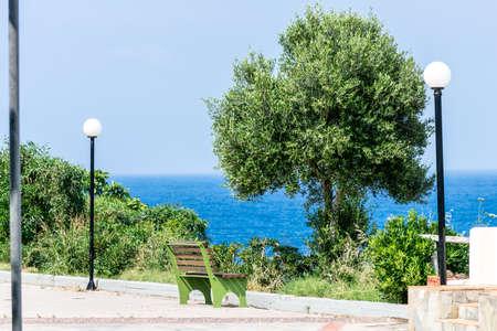 greece shoreline: Bench, tree and lamppost on shoreline in Crete, Greece.