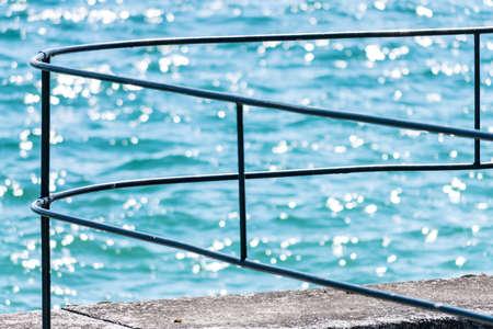 glimmering: Fence on pier by lake geneva, in Switzerland.