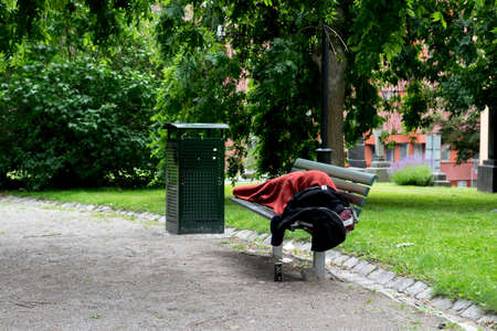 homeless person: Homeless person sleeping in park, on bench. Stockholm, Sweden.
