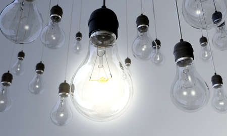 Switched On - An array of hanging light bulbs with the main one turned on Stock Photo - 12861934