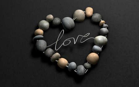Een handgemaakte hartvorm gemaakt van draad en stenen met het woord Liefde gespeld op een steen achtergrond Stockfoto