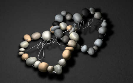 Two handcrafted heart shapes made out of wire and stones one with the word YOU, the other with the word ME