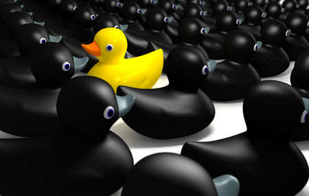 A non-conformist depiction of a yellow rubber bath duck swimming against the flow of black rubber ducks. Stock Photo