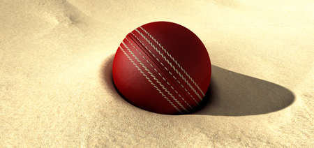 embed: A red leather cricket ball plugged in some desert sand