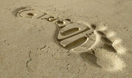 carbon footprint: A footprint in some beach sand with the tread shape spelling out the word carbon