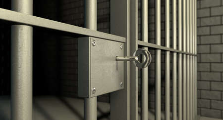 criminal act: A closeup of the lock of a  brick jail cell with iron bars and a key in the locking mechanism Stock Photo