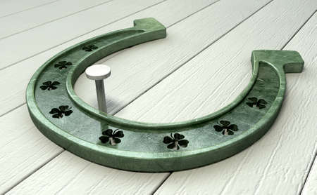 A metal horseshoe with punched out shamrock shapes nailed in place on a wooden background photo