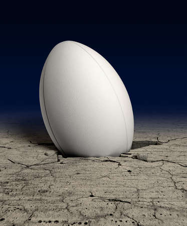 rugby ball: A white dimpled rugby ball stuck in a whole cracked in the ground on a dark background