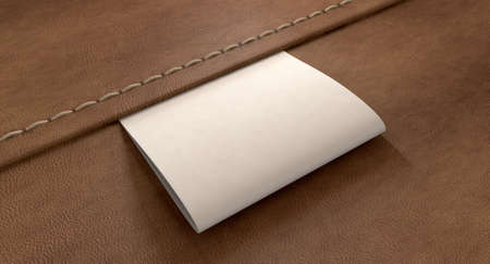 sew tags: A white woven clothing label sewn into seamed brown leather Stock Photo