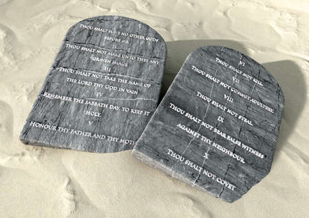 Two stone tablets with the ten commandments inscribed on them lying on brown desert sand photo