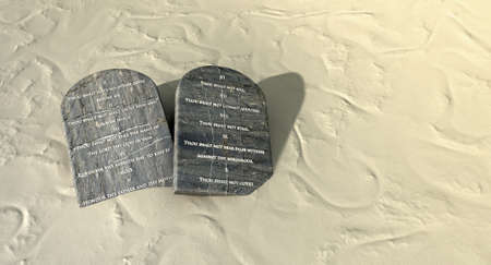 ethics: Two stone tablets with the ten commandments inscribed on them lying on brown desert sand