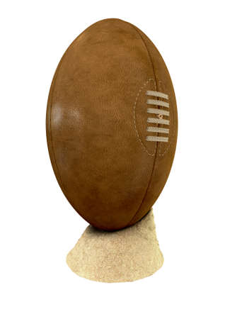 unbranded: An old classic leather rugby ball with laces and stitching placed on a small pile of beach sand on an isolated background