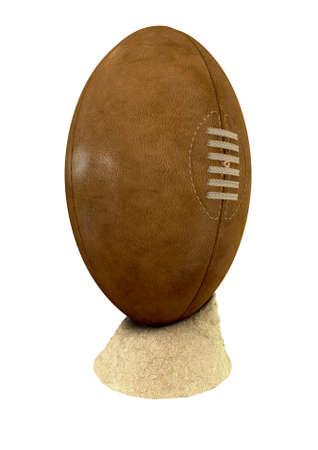 pelota rugby: Una vieja pelota de rugby de cuero clásico con cordones y costuras colocadas en un pequeño montón de arena de la playa en un fondo aislado