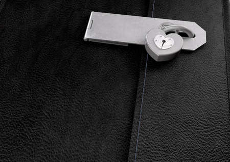 hasp: A closeup of a black leather diary secured by a hasp and a heart shaped padlock