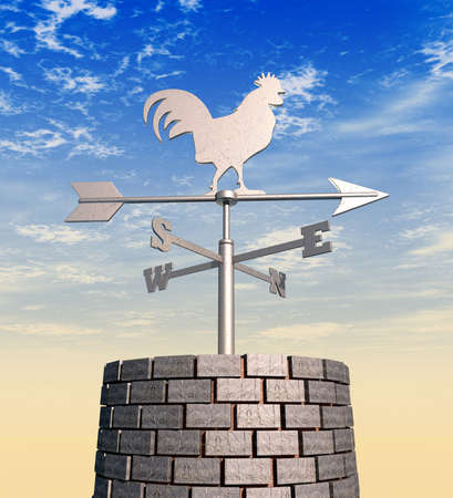 A regular metal weathervane with a cockeral motif facing north on brick chimney against a blue sunny sky backdrop photo