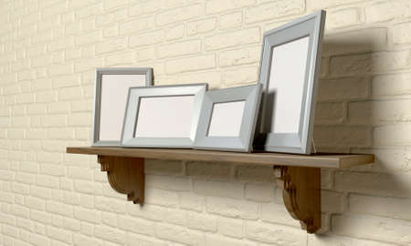 A perspective view of a regular wooden shelf displaying 4 blank metal picture frames on a yellow brick wall photo