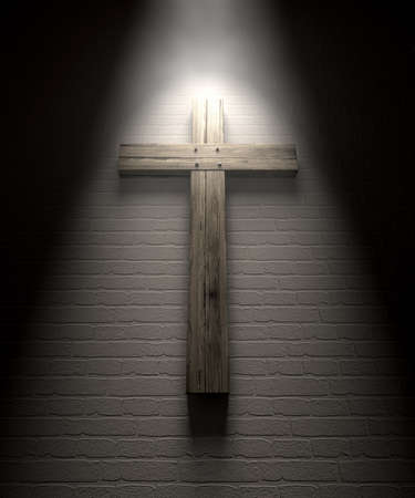 crucifix: A regular wooden crucifix mounted on a white wall under a spotlight Stock Photo