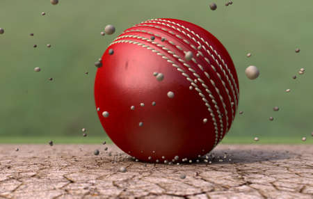 emanating: A red leather stitched cricket ball hitting a cracked cricket pitch with dirt particles emanating from the impact Stock Photo