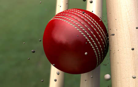 emanating: A red leather stitched cricket ball hitting wooden wickets with dirt particles emanating from the impact Stock Photo