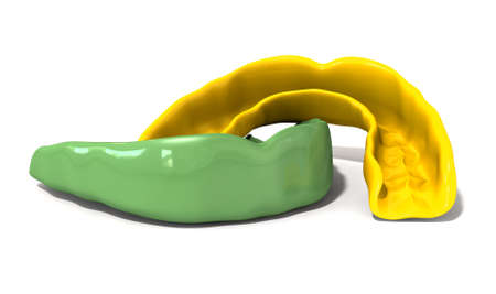 moulded: Two regular yellow and green moulded sports gum guards on an isolated background