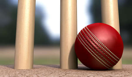 cricket sport: A red leather cricket ball lying on cracked soil at the base of wooden cricket wickets in the daytime