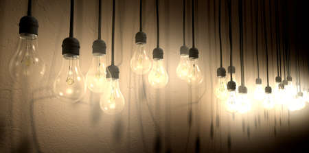 dangling: A front view row of displayed illuminated hanging lightbulbs casting various shadows on a brown wall background Stock Photo