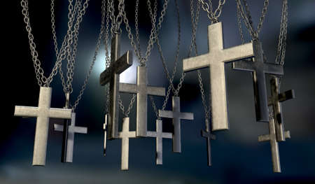 crucifixes: A group of metal crucifixes hanging from chains on a dark background Stock Photo