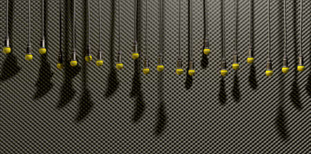 sound proof: A front view of a row of yellow microphones dangling by cords at various heights on a grey acoustic foam wall background