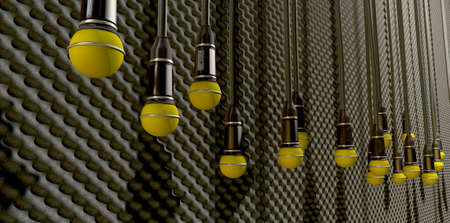 dangling: A front view of a row of yellow microphones dangling by cords at various heights on a grey acoustic foam wall background