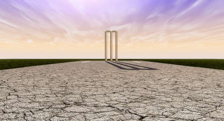 cricket game: The length of a cracked cricket pitch with white markings on a purple and orange sky background with wooden wickets set up in the distance Stock Photo