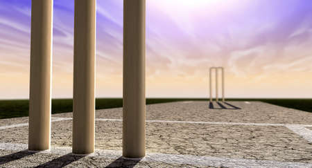 cricket sport: A cracked cricket pitch with white markings on a purple and orange sky background with wooden wickets set up in the foreground and background