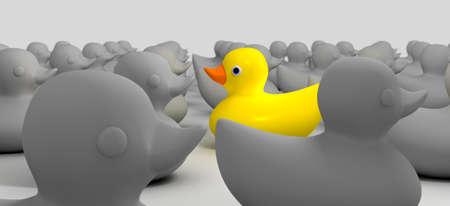 A non-conformist depiction of a yellow rubber bath duck swimming against the flow of a sea of grey rubber ducks Stock Photo