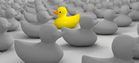 A non-conformist depiction of a yellow rubber bath duck swimming against the flow of a sea of grey rubber ducks Banco de Imagens