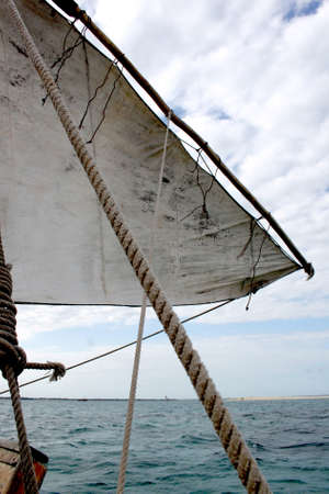 rigging: A closeup of a traditional dhow sail and ropes on emerald blue water in Zanzibar Stock Photo