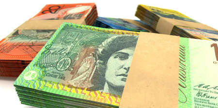 australian money: A scattered pile of australian dollar bank notes bundled into value denominations on an isolated background