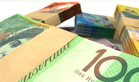 australian dollars: A scattered pile of australian dollar bank notes bundled into value denominations on an isolated background