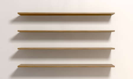 cleared: A front view of four regular cleared wooden shelves on an cream colored wall with copy space Stock Photo