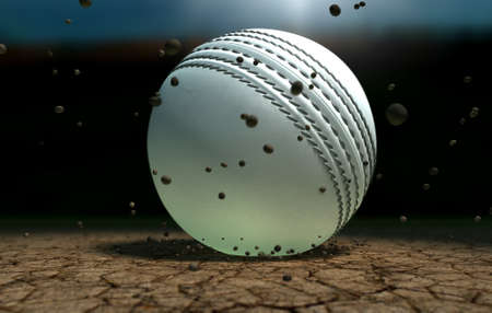 cricket sport: A white leather stitched cricket ball hitting a cracked cricket pitch with dirt particles emanating from the impact at night