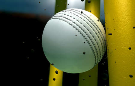 cricket game: A white leather stitched cricket ball hitting yellow wooden wickets with dirt particles emanating from the impact at night Stock Photo