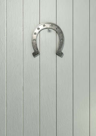 A metal horseshoe with punched out shamrock shapes on a bleach wooden surface photo