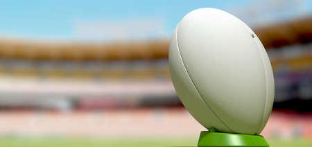 A plain white textured rugby ball on a green kicking tee in a stadium