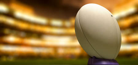 pelota de rugby: Un blanco balón de rugby con textura liso en un tee azul en un estadio en la noche