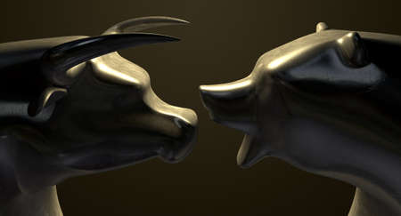 A closeup of two bronze castings depicting a stylized bull and a bear in contrasting light representing a financial market trends on an isolated dark background photo
