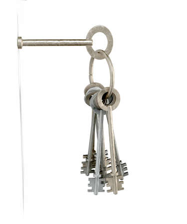 inserted: A set of old keys on a hoop hanging from one inserted into a key hole on a white wall background