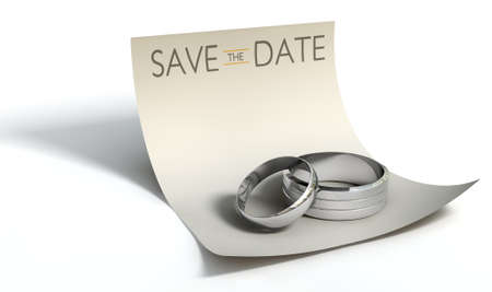 A marriage or engagement concept showing a man and womans silver wedding bands on a curled paper note with a heading saying save the date on an isolated white background photo